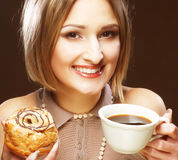 Mujer que come la galleta y que bebe el café. Imagen de archivo