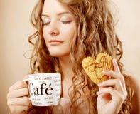 Mujer que come la galleta y que bebe el café. Imagen de archivo libre de regalías
