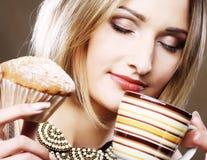 Mujer que come la galleta y que bebe el café. Fotos de archivo