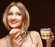 Mujer que come la galleta y que bebe el café. Fotografía de archivo