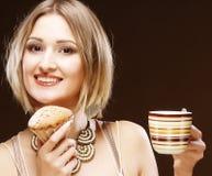 Mujer que come la galleta y que bebe el café Imagenes de archivo