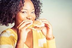Mujer que come la hamburguesa imagenes de archivo