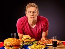 Mujer que come la hamburguesa El estudiante consume los alimentos de preparación rápida Foto de archivo