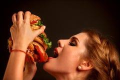 Mujer que come la hamburguesa El estudiante consume los alimentos de preparación rápida Fotografía de archivo