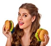Mujer que come la hamburguesa El estudiante consume los alimentos de preparación rápida en la tabla Imagen de archivo libre de regalías