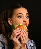 Mujer que come la hamburguesa La muchacha quiere comer los alimentos de preparación rápida Fotografía de archivo