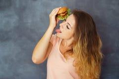 Mujer que come la hamburguesa que mancha las manos con la salsa imagenes de archivo