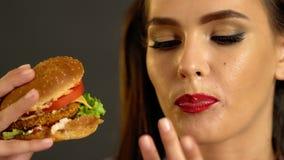 Mujer que come la hamburguesa Mordedura de la muchacha de la hamburguesa muy grande almacen de metraje de vídeo