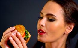 Mujer que come la hamburguesa La muchacha quiere comer los alimentos de preparación rápida Foto de archivo