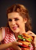 Mujer que come la hamburguesa y guiños El estudiante feliz come el almuerzo del bocadillo Foto de archivo