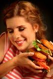 Mujer que come la hamburguesa y guiños El estudiante feliz come el almuerzo del bocadillo Fotos de archivo