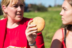 Mujer que come la hamburguesa y las patatas fritas Foto de archivo