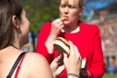 Mujer que come la hamburguesa y las patatas fritas Fotos de archivo
