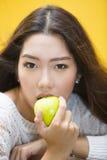 Mujer que come la manzana verde Imagenes de archivo