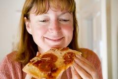 Mujer que come la pizza de salchichones Fotos de archivo libres de regalías