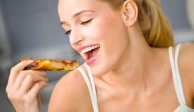 Mujer que come la pizza en la cocina Fotografía de archivo