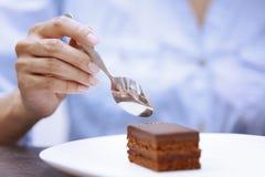 Mujer que come la torta de chocolate Imagen de archivo libre de regalías