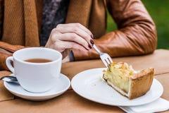 Mujer que come la torta de la picadura de abeja, al aire libre Foto de archivo libre de regalías