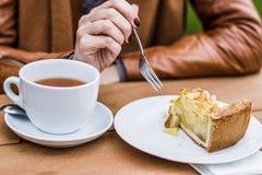 Mujer que come la torta de la picadura de abeja, al aire libre Fotos de archivo