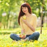 Mujer que come las frutas en el parque Imagen de archivo libre de regalías