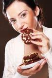 Mujer que come las galletas de microprocesador de chocolate Imagenes de archivo
