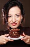 Mujer que come las galletas de microprocesador de chocolate Imagen de archivo libre de regalías