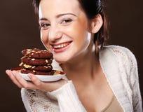 Mujer que come las galletas de microprocesador de chocolate Fotos de archivo