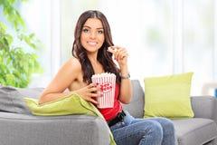 Mujer que come las palomitas asentadas en el sofá en casa imagenes de archivo