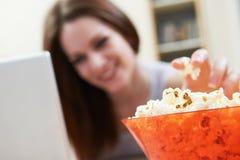 Mujer que come las palomitas mientras que mira película en el ordenador portátil Imagen de archivo
