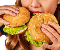 Mujer que come las patatas fritas y hamburguesa y alimentos de preparación rápida Imagen de archivo