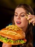 Mujer que come las patatas fritas y la hamburguesa Imagenes de archivo