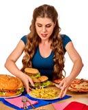 Mujer que come las patatas fritas y la hamburguesa Foto de archivo