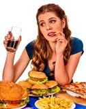 Mujer que come las patatas fritas y la hamburguesa Foto de archivo libre de regalías