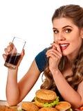 Mujer que come las patatas fritas y la hamburguesa Imagen de archivo