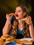 Mujer que come las patatas fritas y la hamburguesa con la pizza Imagen de archivo libre de regalías