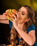 Mujer que come las patatas fritas y la hamburguesa con la pizza Fotografía de archivo libre de regalías
