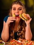 Mujer que come las patatas fritas y la hamburguesa en la tabla Imagenes de archivo