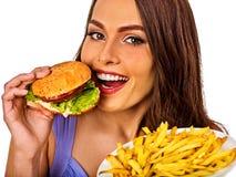 Mujer que come las patatas fritas y la hamburguesa en la tabla Foto de archivo libre de regalías