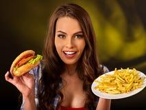 Mujer que come las patatas fritas y la hamburguesa en la tabla Imagen de archivo libre de regalías