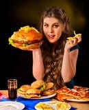 Mujer que come las patatas fritas y la hamburguesa en la tabla Foto de archivo
