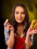 Mujer que come las patatas fritas y la hamburguesa en la tabla Fotos de archivo