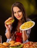 Mujer que come las patatas fritas y la hamburguesa en la tabla Fotos de archivo libres de regalías