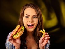 Mujer que come las patatas fritas y la hamburguesa en la tabla Fotografía de archivo