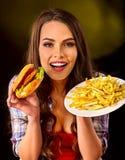 Mujer que come las patatas fritas y la hamburguesa en la tabla Imágenes de archivo libres de regalías