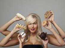 Mujer que come las tortas de la crema Imagenes de archivo