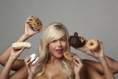 Mujer que come las tortas de la crema Fotos de archivo