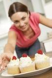 Mujer que come las tortas en cocina fotos de archivo