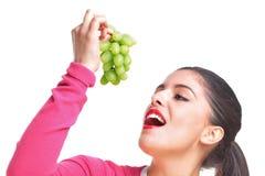 Mujer que come las uvas foto de archivo libre de regalías