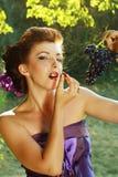 Mujer que come las uvas al aire libre en el parque Imagen de archivo libre de regalías