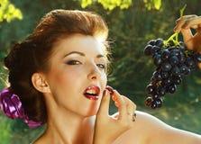 Mujer que come las uvas al aire libre en el parque Fotos de archivo libres de regalías